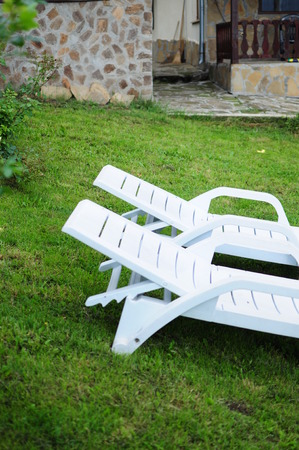Two white chairs on a lawn