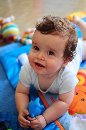 Baby lying on tummy, playing with toy Standard-Bild