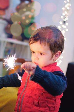 Little kid holding a sparkling stick Standard-Bild