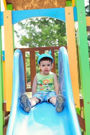Little boy on a blue slide Standard-Bild