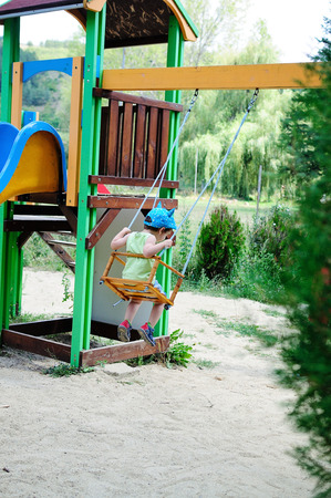 Little boy on a swing on a hot summer day