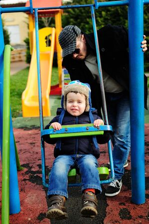 Happy little boy enjoying the swing on a cold day, his father behind