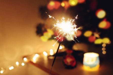 Sparkle stick  with lights and christmas tree on the background