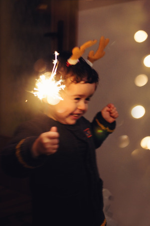 Little happy kid holding a sparkling stick and dancing with joy