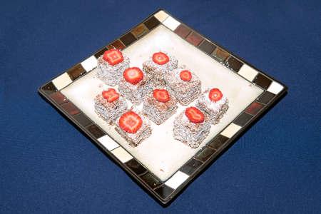 lamington: Lamington squares on a plate on top of a blue napkin or serviette