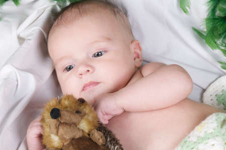 baby lying with fury toy with eyes open