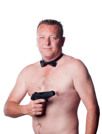 nipple piercing: caucasian male with black bow tie pointing a gun Stock Photo