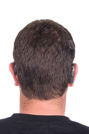 young deaf or hearing impaired man with cochlear implant and hearing aid photographed from behind to show device Stock Photo - 26329718
