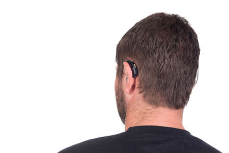 impaired: young deaf or hearing impaired man with cochlear implant and hearing aid photographed from behind to show device