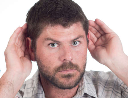 cochlear: close up of a deaf man with cochlear implant cupping both ears to hear