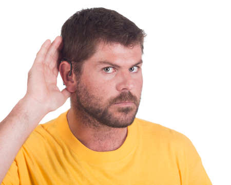 impaired: young deaf or hearing impaired man cupping one ear to listen Stock Photo