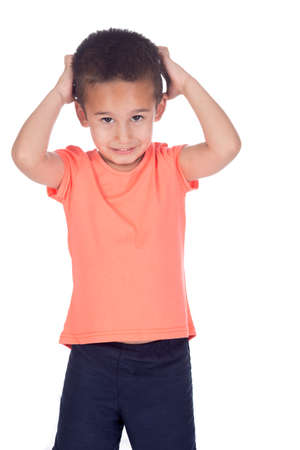 little boy with orange shirt and short brown hair posing in studio on a white background scratching an itchy head photo