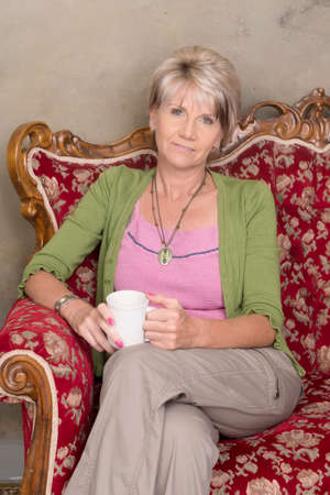 middle aged caucasian woman with  green jersey, pink top and brown pants with a cup of coffee sititng on a red flowered couch in studio photo