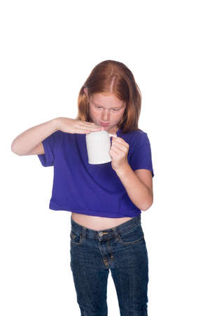red head girl: young red head girl in purple shirt making sure the cup is empty Stock Photo