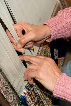 knotting: Donna seduta e annodare un tappeto turco su un telaio con i vari colori di lana