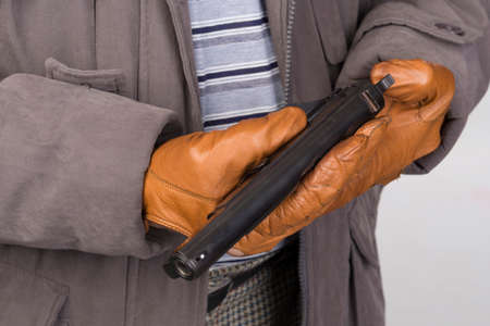 close of of a man in gloves holding a pistol in both hands. only hands and fire-arm is visible in the photo. photo