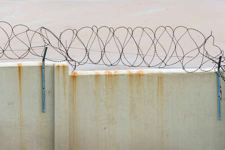 keepout: Barbed wire on a wall