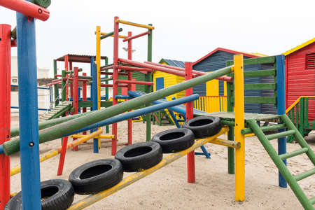 jungle gym: colorful childrens playground or jungle gym in red, yellow green and blue on the beach next to beach huts on an overcast day