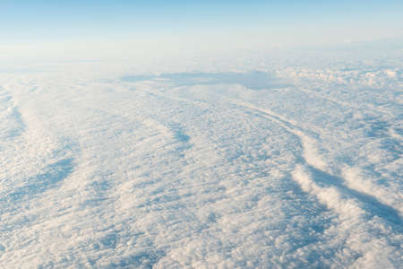 Blanket of white clouds as seen from a airplane window in early morning light
