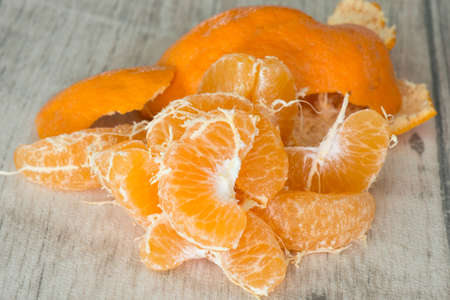 Peeled tangerine wedges on a wooden table photo