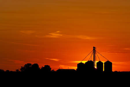 A silhouette of Midwestern grain bins against a beautiful setting sun