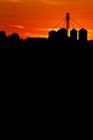 Vertical shot of grain bins silhouetted against a bright, orange sunset