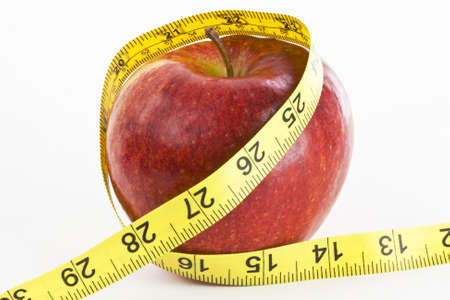 consuming: An apple is wrapped with a yellow tape measure to convey that healthy eating assists in weight loss. Stock Photo