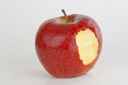 Een heldere rode appel geïsoleerd op wit met een hap uit het  Stockfoto