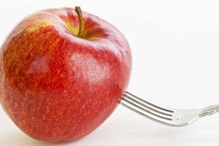 Een grote, lichte rode appel is gestoken door een vork tegen een witte achtergrond Stockfoto