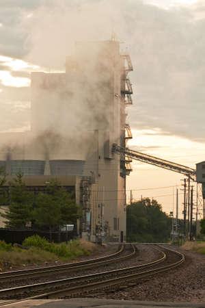 Train tracks skirt around a coal electric plant