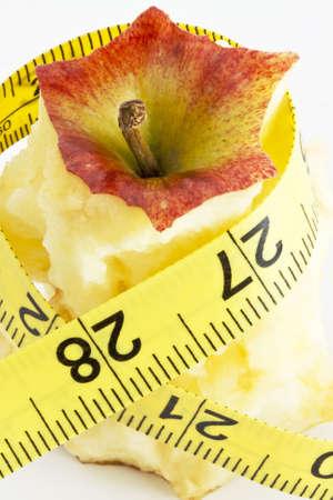 Een verticale foto van een gegeten appel en verpakt met een meetlint