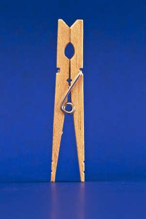 Een verticaal beeld van een wasknijper die op blauw wordt geïsoleerd