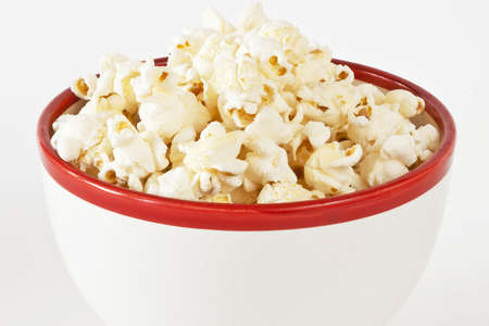 A closeup of a white and red bowl of popcorn isolated on white