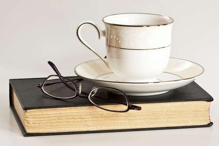 Een kopje thee en een bril zitten bovenop een zwart boek.