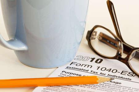 Mok, bril en potlood zitten bovenop een 2010 1040 belastingformulier. Stockfoto