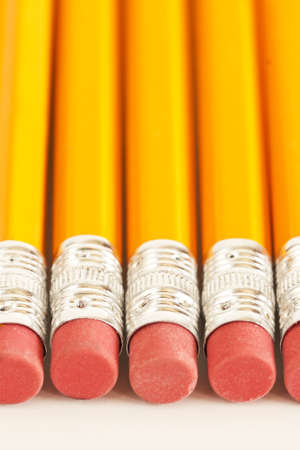A line of pencils sits on top a white background.