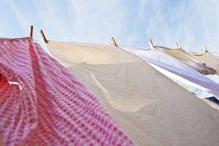 Een rij van kleren hangt aan een kleding lijn backdropped door een blauwe hemel Stockfoto