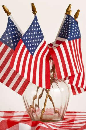 Een vaas gevuld met Amerikaanse vlaggen zit op een rode pastel tabel doek.  Symboliseert picknicks en 4 juli.