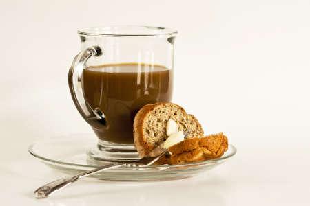 Een glazen mok van koffie zit bovenop een glasplaat met beboterde muffin.  Geweldig om te symboliseren een ontbijt maaltijd.  Ruime typespace. Stockfoto