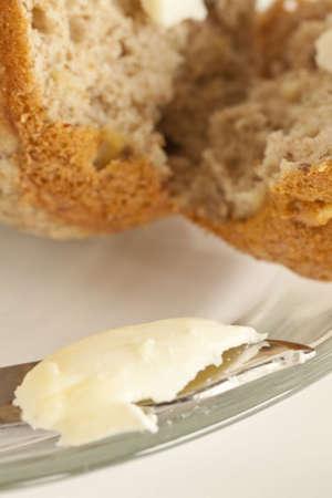 Een boter mes en split muffin zitten op de top van een glasplaat. Stockfoto