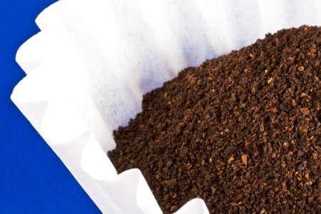 Een stapel van koffie gronden zit in een witte filter op de top van blauw. Stockfoto