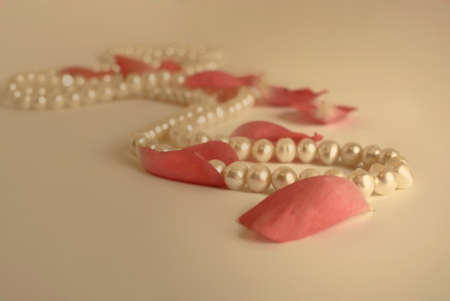 pink pearl: vintage style pearl necklace and rose petals background