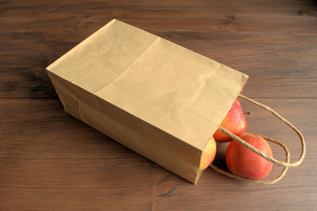 apple paper bag: Apples. Paper bag with apples lay on a brown wooden surface. From bags rolled three ripe red apple.