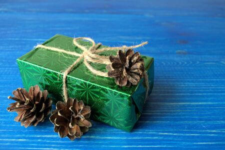 pine three: Christmas. Christmas gift box with lying on a wooden surface. Capsule green, tied with string. Nearby are three pine cones. Stock Photo