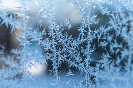 Frosty pattern on transparent glass. Winter background