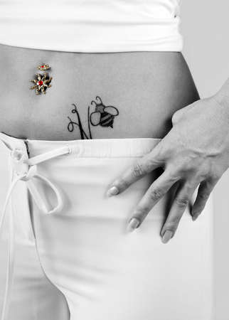 navel piercing: woman with tattoo and piercing