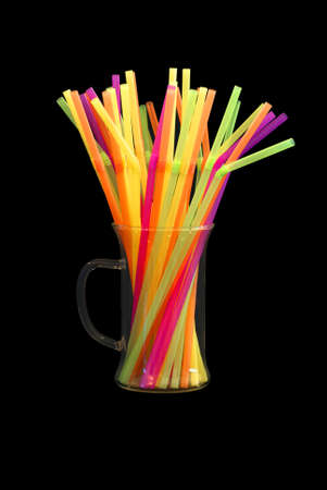 Colorful Straws in a Coffee mug that pop against the isolated black background. photo