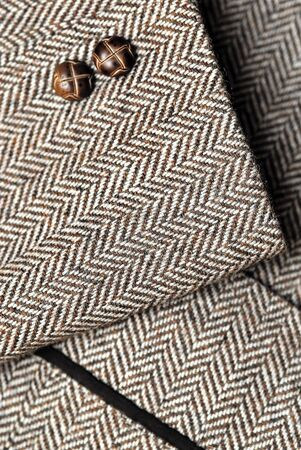 tweed: close-up of sleeve of tweed brown jacket with buttons