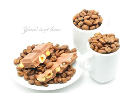 two cups and plate filled with coffee beans and chocolate isolated Stock Photo - 7548944