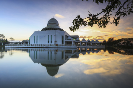 Stunning vibrant sunrise over An nur Mosque, Seri Iskandar Perak. Soft focus and nature composition.  Long exposure was used to create smooth water on the lake.
